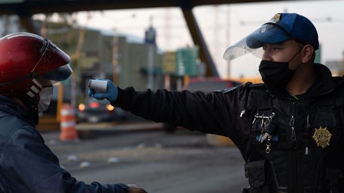A police officer measures the body temperature of a man