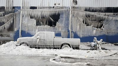 Cars were frozen solid after a torrent of water was sprayed on the warehouse. (AAP)