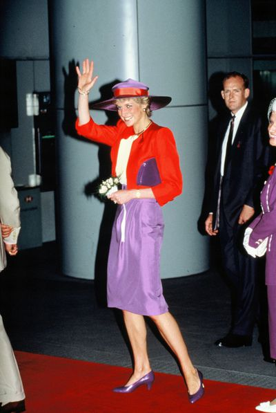 Diana, Princess of Wales in a vibrant red and purple outfit in Hong Kong, November 1989