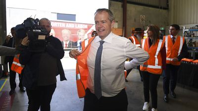 Bill Shorten dons a high vis vest during a visit to Volgren Bus Manufacturing facility in Perth.