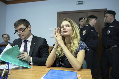 Veronika Nikulshina, center, a member of the feminist protest group Pussy Riot, attends hearings in a court in Moscow, Russia, Monday, July 23, 2018. Four members of the feminist protest group Pussy Riot, who had run onto the pitch dressed in police uniforms during the World Cup final, were sentenced in Moscow City Court on Monday. (AP Photo/Pavel Golovkin)