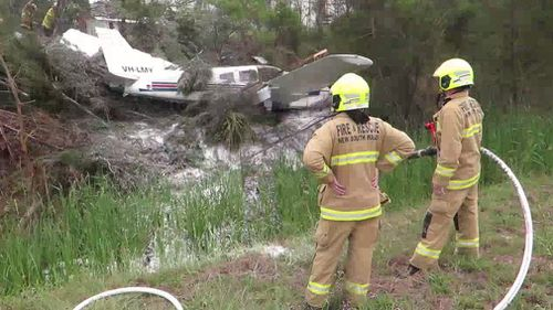 Fire crews attend to the wreckage of the plane. (9NEWS)