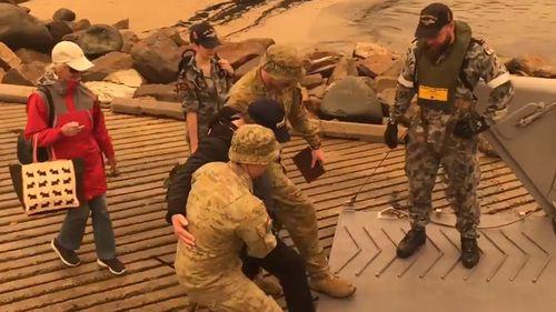 Troops help an elderly gentleman evacuate in Mallacoota.