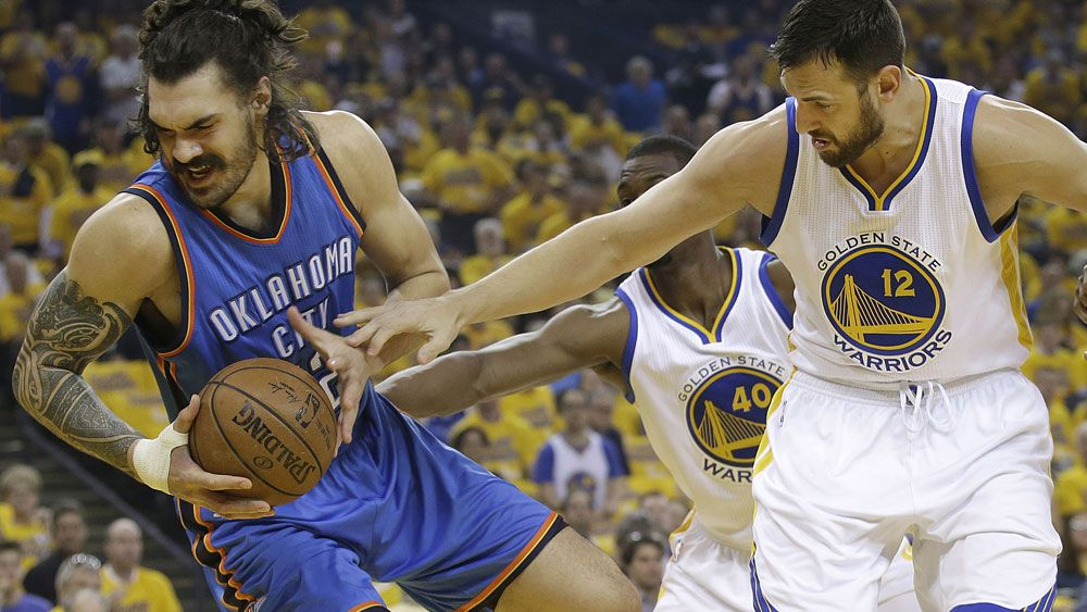 Andrew Bogut (right) reaches in against Steven Adams. (AAP)
