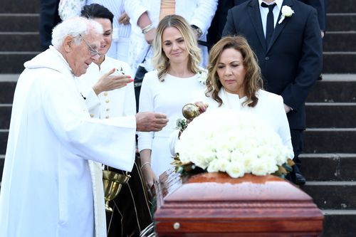 Les Murray's partner Maria (right) blesses the casket as his daughters Tania (left) and Natalie look on following his State Funeral at St Mary's Cathedral. (AAP)