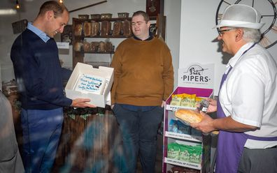 Prince William, Duke of Cambridge is presented with a birthday cake by shop owner Paul Brandon (right) during a visit to Smiths the Bakers, in the High Street on June 19, 2020 in King's Lynn, Norfolk.