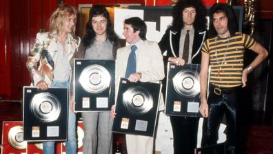 The members of Queen with their agent, John Reid.