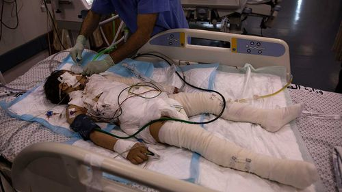 A Palestinian medic gives treatment to a wounded girl in the ICU of the Shifa hospital in Gaza City.