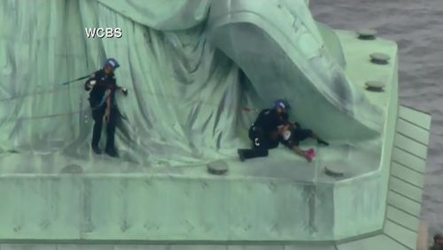 The officers have grabbed the woman and are pulling her down from the base of the statue. Picture: Supplied