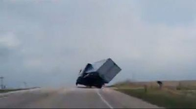 A truck teeters on the brink of toppling over on a US highway.