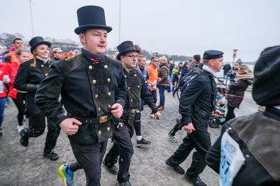 Chimney sweeps in their working clothes take part in the New Year's Eve run in Hannover.
