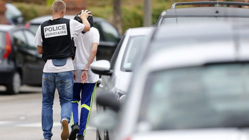 A French policeman arrests a man following a search of a house in the Normandy city of Saint-Etienne-du-Rouvray. (AFP)