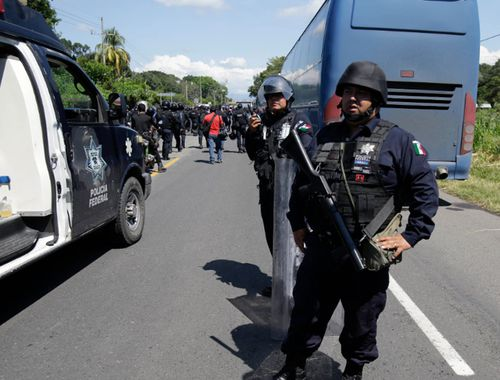 Mexican federal police stand guard along the road being used by a U.S.-bound, large caravan of Central American migrants.
