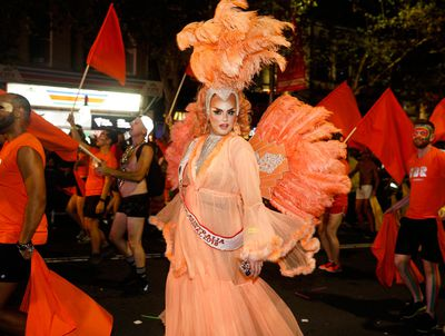 Orange feathers were a feature of this drag queen's outfit. (AAP)