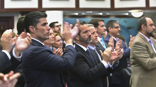 Florida House sponsor Rep. Jose Oliva (second from left) is joined by other House members in applause after a school safety bill passed the House on Wednesday. (AAP)
