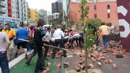 Passersby rush to clear the debris from the wall collapse.