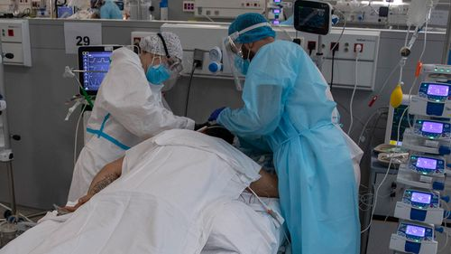 Healthcare staff wearing PPE treat a COVID-19 patient at a hospital in Madrid, Spain.