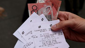 A woman shows off her Melbourne Cup bets. (AAP file image)