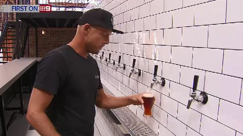 Mick Fanning taste-tests a beer at the Balter brewery. (9NEWS)