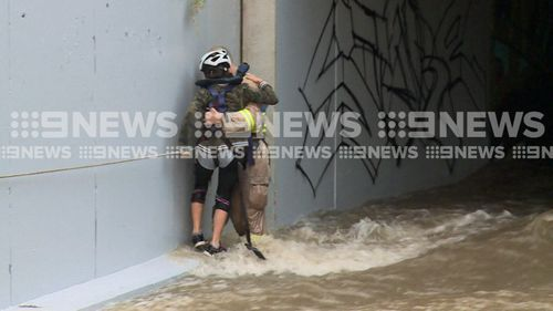 A firefighter rescuing a girl from an aqueduct in Melbourne's south-east.
