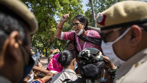 An Indian activist shouts slogans as she is detained by police during a protest in New Delhi.