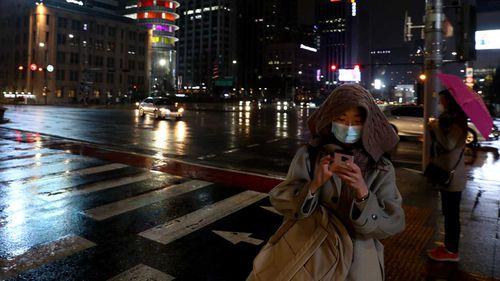 Pedestrians in Seoul, South Korea, wear face masks.