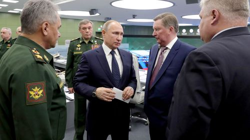 Defence Minister Sergei Shoigu, Army General Valery Gerasimov, Russian President Vladimir Putin, and Russian special presidential representative Sergei Ivanov speak at the National Defense Control Center in Moscow.
