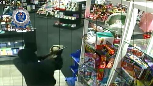 Police are hunting a masked man who was caught on CCTV in a Cessnock newsagency last month with a shotgun. Picture: Supplied.