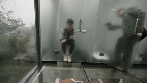 The toilet cubicles are separated by a thin layer of frosted glass. (AAP)