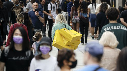 People walk with bags after shopping at the Selfridges department store in London, Monday, June 15, 2020.