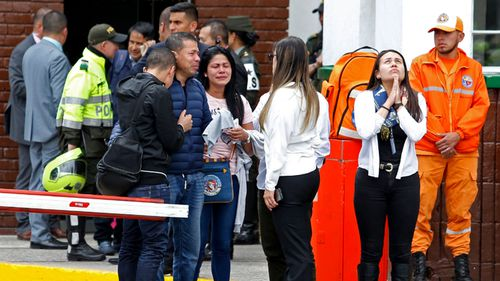 Family members of victims of the bombing gather outside the entrance to the General Santander police academy where the bombing took place in Bogota, Colombia.