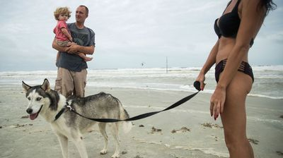 Beachgoers in Jacksonville, Florida, took their dog for a walk before the winds became too strong. (AP)