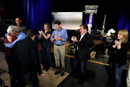 Scientists and other NASA officials applaud and embrace after a mission briefing for the Mars Exploration Rover Opportunity at NASA's Jet Propulsion Laboratory in California.