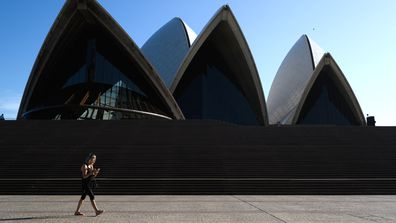 A woman walking in front of a nearly deserted Sydney Opera House. Sydney is seeing a dramatic reduction in people on the streets as people are asked to enact social distancing and self isolation in order to prevent the spread of Covid-19.