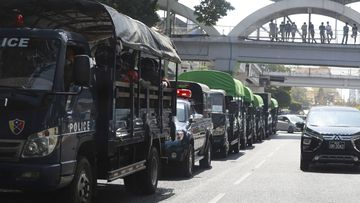 Policemen sit inside trucks parked on a road in the downtown area of Yangon, Myanmar.