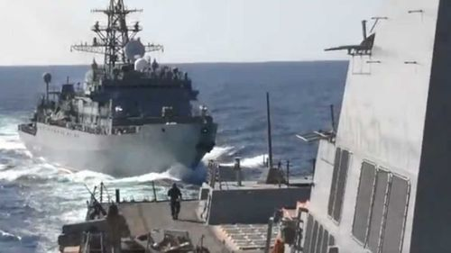 Footage from the US Fifth Fleet shows the Russian ship narrowly closing in on the USS Farragut.