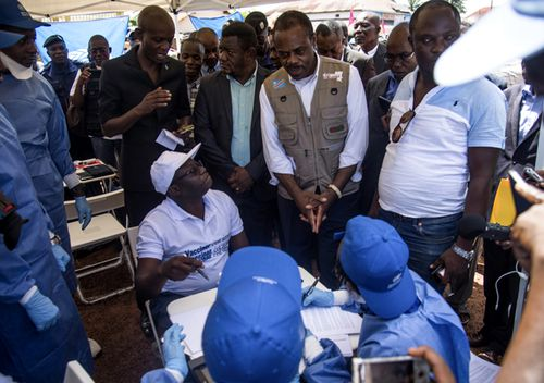 Congo's Health minister Oly Ilunga (seated centre) speaks with other workers during the launch of an experimental Ebola vaccine in Mbandaka, north-western Democratic Republic of the Congo. (AAP)