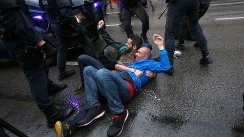 Three man hold to each other as they try to block a Spanish police van from approaching a voting site. (AP)