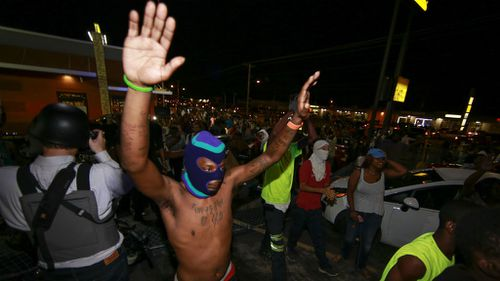 Demonstrators raise their hands during a rally on West Florissant Avenue. (Getty Images)