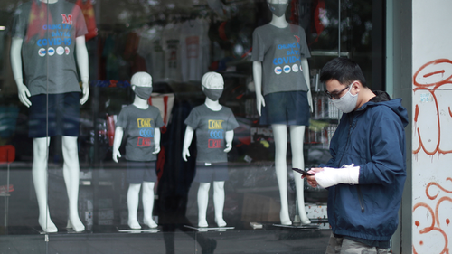 A man walks past the display window of a clothing store in Hanoi, Vietnam on Thursday, Apr. 23, 2020. Business activities have begun to resume in Vietnam as the country lifts the nationwide lockdown to contain the spread of COVID-19. (AP Photo/Hau Dinh)