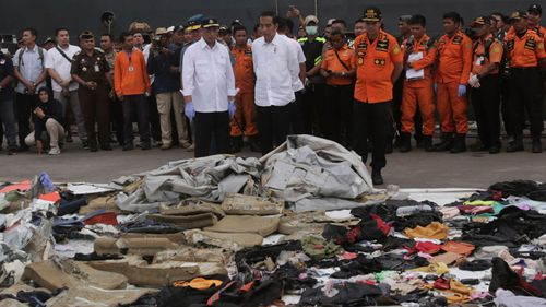 Indonesian President Joko Widodo views debris collected after the two-month-old plane plummeted into the ocean.