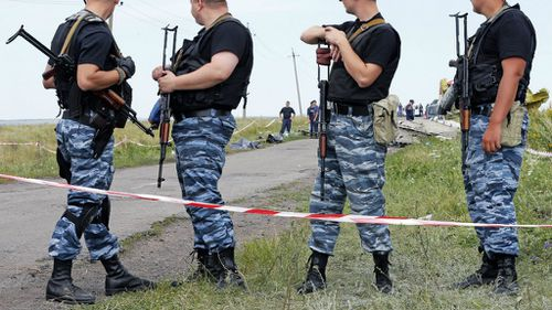 Armed pro-Russian rebel soldiers guard the MH17 crash site in Ukraine. (AAP)