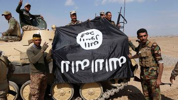 Iraqi government forces hold an ISIS group flag. (AFP)
