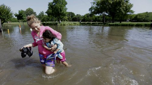 Nayeli Cervantes carries her friend's daughter Sophia Aviles through the floodwaters outside their apartment in Houston. (AAP)
