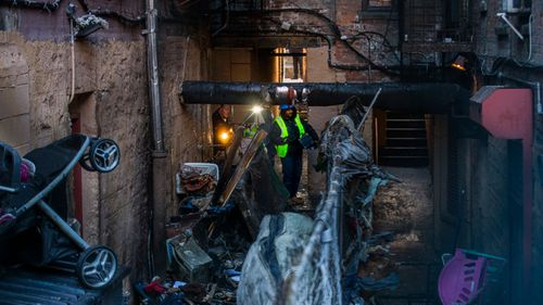 Police and workers inspect the building where at least 12 people died in a fire in the Bronx borough of New York.