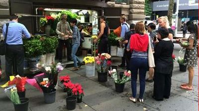Workers line-up at a kiosk in Martin Place to buy flowers to place near the site of the Lindt Cafe siege. (Twitter/@abcnews)