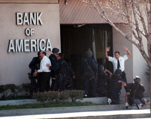 A bank employee holds up his hands as Los Angeles Police and SWAT units search for more robbery suspects inside the Bank of America