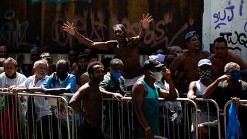 A group made up of homeless people, street vendors, and people in situations of social vulnerability line up at a food distribution centre in Rio de Janeiro, Brazil.