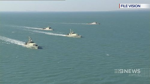 Australian naval and customs ships move in on a smuggling vessel. (9NEWS)