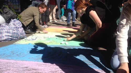 Protesters used chalk to draw a rainbow on the walkway outside the building. (Twitter/ @jgillieatt)